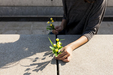 Close-up of woman holding yellow flower on concrete - VABF01550