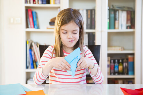 Girl tinkering with paper on table at home - LVF06855