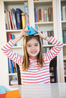 Portrait of smiling girl putting on selfmade paper hat at home - LVF06858