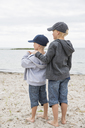 Boys in baseball caps standing at beach - FOLF06984