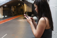 Young woman texting at gym - FOLF07092