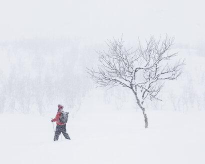 Woman walking through snow with hiking poles - FOLF07170
