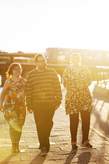 Woman with down syndrome walking with friends along sidewalk at sunset - FOLF07236