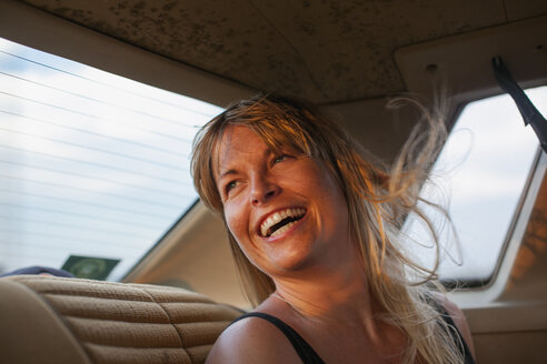 Blonde woman laughing on back seat of car - FOLF07254