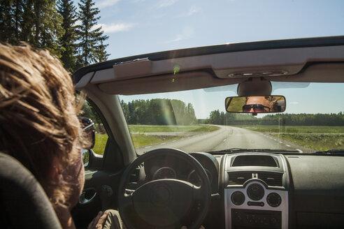 Man driving car along country road at sunlight - FOLF07257