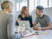 Three professionals talking at desk - FOLF07263
