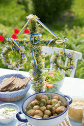 Fresh potatoes and herring in jar on table decorated with flower wreaths - FOLF07470