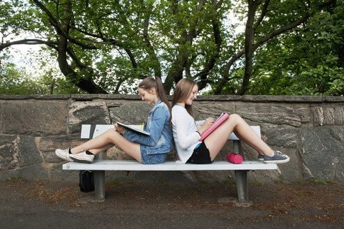 Two teenage girls sitting on bench back to back - FOLF07503