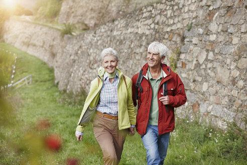 Happy senior couple hiking hand in hand - RORF01249