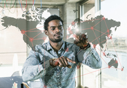 Casual businessman touching glass pane with world map in office - UUF13184