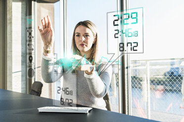 Young businesswoman touching projection screen with data in office - UUF13193