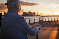 Senior man sitting on promenade at sunset - CAVF33490