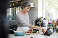 Mature woman using digital tablet while cooking in kitchen - CAVF33565