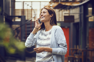 Cheerful woman answering smart phone outside cafe - CAVF33577