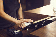 Midsection of owner using digital tablet at checkout counter in coffee shop - CAVF33589