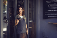 Portrait of confident female owner holding tray with coffee cup outside cafe - CAVF33595