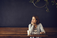 Thoughtful woman looking away while sitting at cafe table - CAVF33604