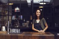 Portrait of happy female owner standing in coffee shop - CAVF33607