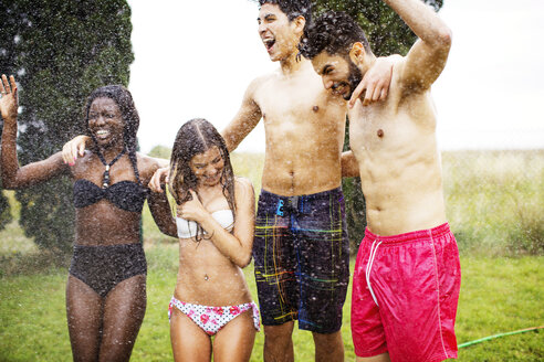 Cheerful friends in swimwear enjoying water spray at yard - CAVF33715
