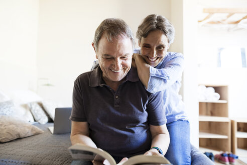 Cheerful senior couple reading book in bedroom - CAVF33727