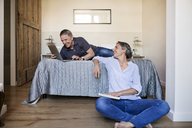 Happy woman looking at senior man using laptop in bedroom - CAVF33730