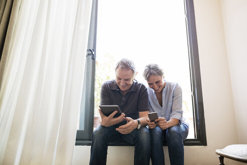 Senior couple using smart phone and tablet computer while sitting on window sill at home - CAVF33742