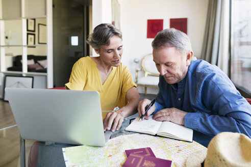 Mature woman planning vacation with man at home - CAVF33745
