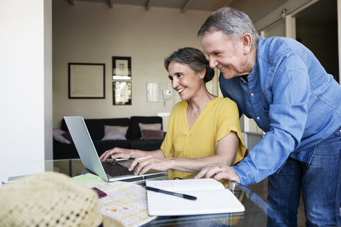 Senior couple using laptop while planning vacation at home - CAVF33748