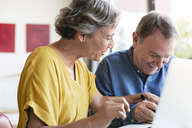 Cheerful senior couple planning vacation at home - CAVF33754