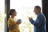Side view of senior couple having coffee by window at home - CAVF33766