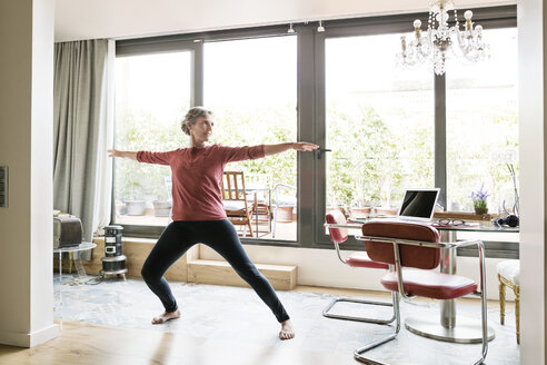 Mature woman practicing yoga in Warrior 2 pose at home - CAVF33775