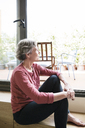 Thoughtful mature woman looking through window at home - CAVF33781