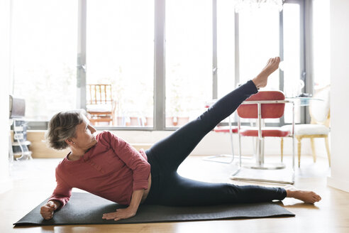 Determined mature woman exercising on floor at home - CAVF33790