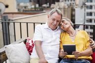 Loving senior couple sitting on bench at terrace - CAVF33805