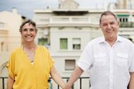 Portrait of happy senior couple standing on terrace - CAVF33808
