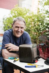 Portrait of happy senior man repairing vintage radio at yard - CAVF33826