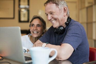Happy senior couple using laptop at home - CAVF33832