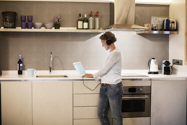 Side view of mature woman using laptop at kitchen counter - CAVF33835
