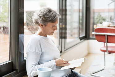 Side view of mature woman reading book at home - CAVF33838