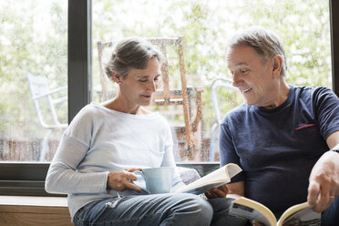 Happy senior couple reading books while sitting by window at home - CAVF33841
