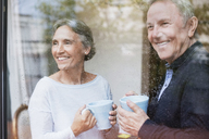 Happy senior couple holding coffee mugs while looking through window at home - CAVF33844