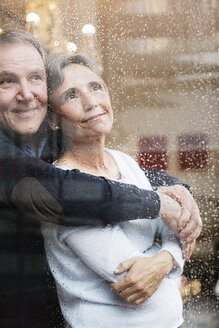 Loving senior couple looking through wet window - CAVF33847