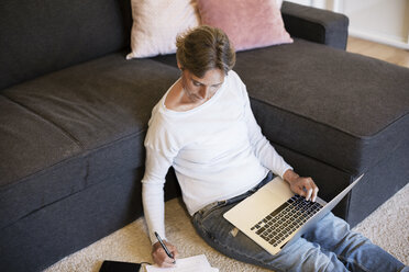 High angle view of mature woman writing while using laptop at home - CAVF33850