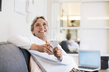Cheerful mature woman holding smart phone while sitting on sofa at home - CAVF33853