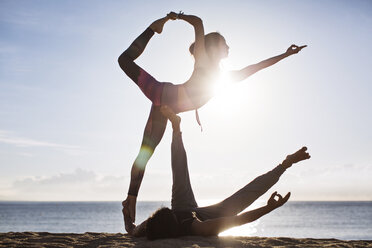 Couple doing yoga on beach against sky during summer - CAVF33865