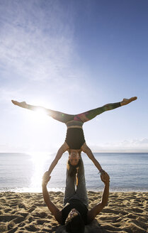 Determined multi-ethnic couple doing yoga on shore against sky - CAVF33868
