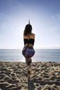 Rear view of woman performing yoga in eagle pose on beach against sky - CAVF33871