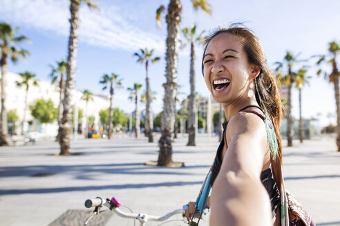 Portrait of cheerful woman riding bicycle on road during summer - CAVF33880