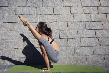 Determined woman doing arm balance yoga pose on sidewalk - CAVF33892