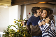 Man kissing girlfriend while standing by Christmas tree at home - CAVF33931